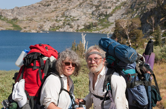 Nita Winter and Rob Badger carrying 65 and 85 pound backpacks by Winnemucca Lake in the Sierra Nevada Mountains.