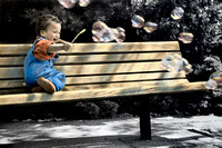 Young 2 year old African American boy playing with bubbles on park bench