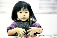 Young Asian American girl finger painting at the Discovery Museum, Saualito, California. San Francisco Bay Area. Photographed by Nita Winter.
