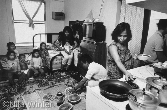 Cambodian family eating dinner in tiny apartment in San Francisco's Tenderloin District