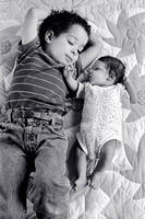 Brother and newborn sister on sunflower quilt _grayscale