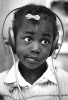 Girl listening to story about tiger on earphones_Childcare center Tenderloin San Francisco