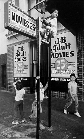 Children playing and climbing parking sign outside adult bookstore Tenderloin San Francisco CA